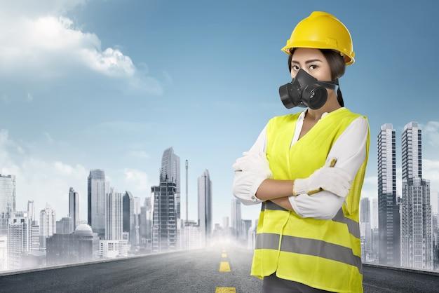 Jonge aziatische vrouwelijke bouwvakker met gele helm en eenvormig