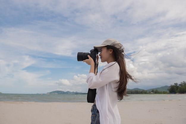 Jonge aziatische vrouwelijke fotograaf met camera in openlucht bij strand in thailand