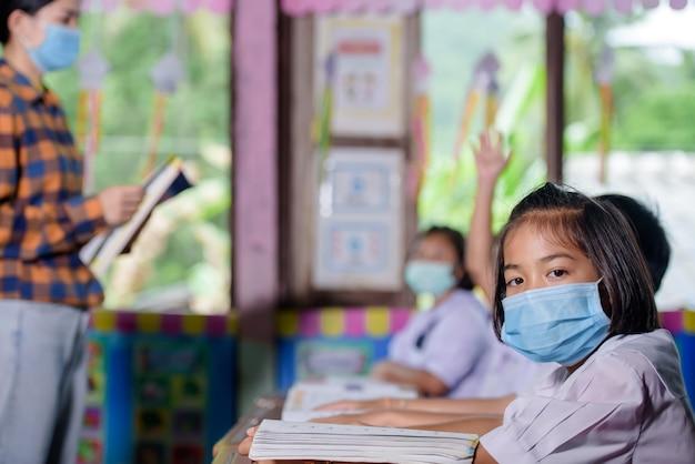 Jonge aziatische vrouwelijke leraar die een medisch gezicht draagt en studenten in een landelijke thaise dorpsschool leren