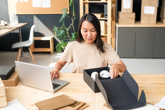 Jonge aziatische vrouwelijke manager van een online winkelkantoor die een koptelefoon in een zwarte doos zet op de werkplek terwijl ze bestellingen van klanten inpakt