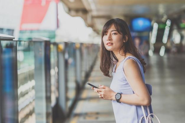 Jonge aziatische vrouwelijke passagier die de tijd controleert en wacht op haar vriend in de metro