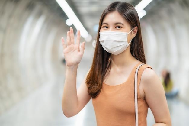 Jonge aziatische vrouwelijke passagier die een chirurgisch masker draagt en naar de camera kijkt om hallo te zeggen