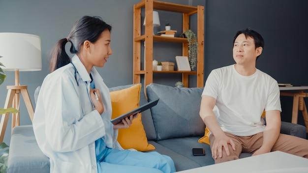 Jonge aziatische vrouwelijke professionele arts arts die digitale tablet gebruikt die goed nieuws van de gezondheidstest deelt met gelukkige mannelijke patiënt zit op bank in huis