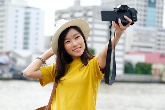 Jonge aziatische vrouwelijke reiziger die selfie foto in stad in openlucht nemen
