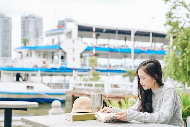 Jonge aziatische vrouwelijke student zittend aan tafel op de campus en het lezen van een boek bij het klaarmaken voor examens