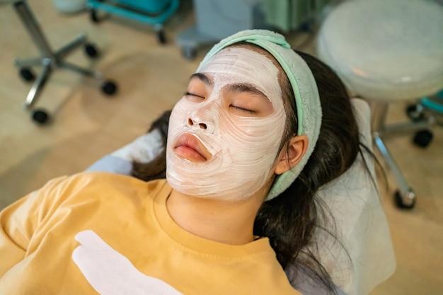 Jonge aziatische vrouwelijke tiener die haar acne krijgt