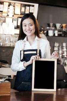 Jonge aziatische vrouwen barista die leeg bord met het glimlachen gezicht houden bij koffie tegenachtergrond, kleine bedrijfseigenaar, voedsel en drank de industrieconcept