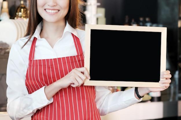Jonge aziatische vrouwen barista die leeg bordmenu met het glimlachen gezicht houden bij koffie tegenachtergrond