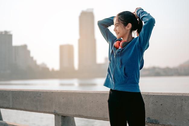 Jonge aziatische vrouwen bonden hun haar vast ter voorbereiding op een ochtendoefening in de stad city running