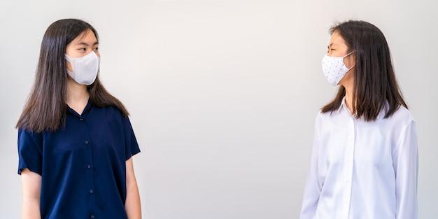Jonge aziatische vrouwen, die een masker dragen en zich op een veilige afstand van elkaar bevinden terwijl ze met elkaar praten