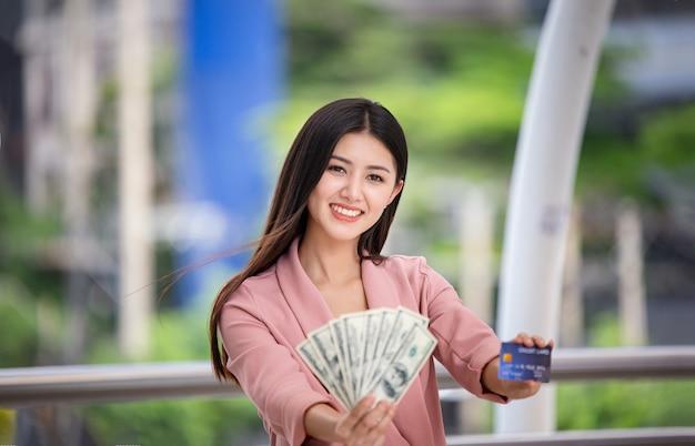 Jonge aziatische vrouwen die geld en creditcard houden bij openlucht.