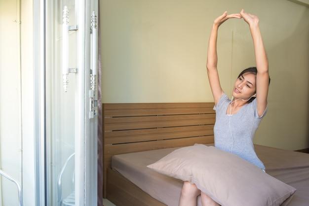 Jonge aziatische vrouwen die in de ochtend op het bed opstaan, handen omhoog ophieven.