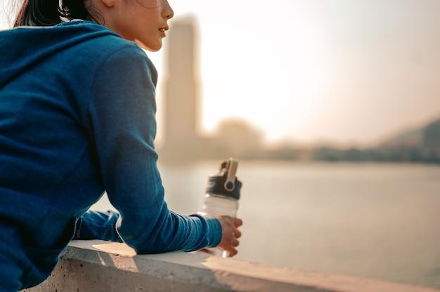 Jonge aziatische vrouwen die staan om het uitzicht op de stad te zien na een ochtendtraining in de stad te hebben gejogd
