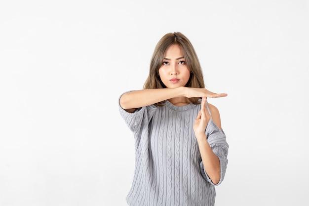 Jonge aziatische vrouwen die tijd uit gebaar met handen doen