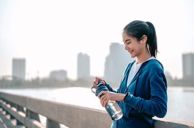 Jonge aziatische vrouwen drinken water en rusten uit na een ochtendtraining in de stad
