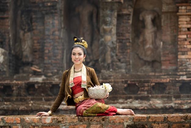 Jonge aziatische vrouwen in traditionele kleding zitten op oude muur en houden zilveren strik ot lotus in de hand. mooie meisjes in klederdracht. thais meisje in retro thaise kleding.