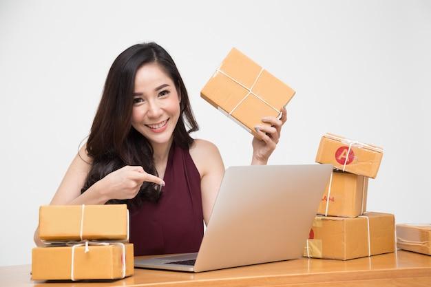 Jonge aziatische vrouwen met startende zelfstandige ondernemer die thuis werkt en enthousiast zijn over de bestellingen van veel klanten, levering van online marketingverpakkingen, thais model
