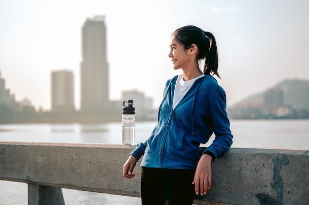 Jonge aziatische vrouwen staan te rusten na het joggen van een ochtendtraining in de stad een stad die leeft