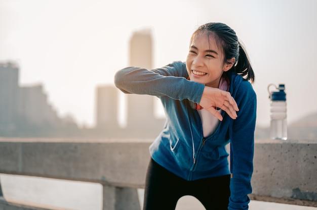 Jonge aziatische vrouwen vegen zweet af na een ochtendtraining in de stad een stad die gezond leeft i