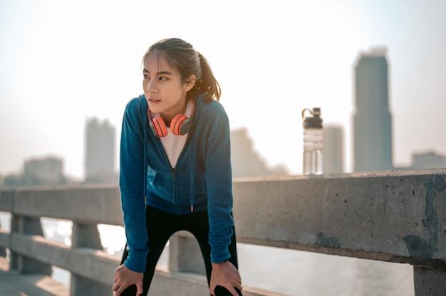 Jonge aziatische vrouwen vegen zweet af na een ochtendtraining in de stad een stad die gezond leeft