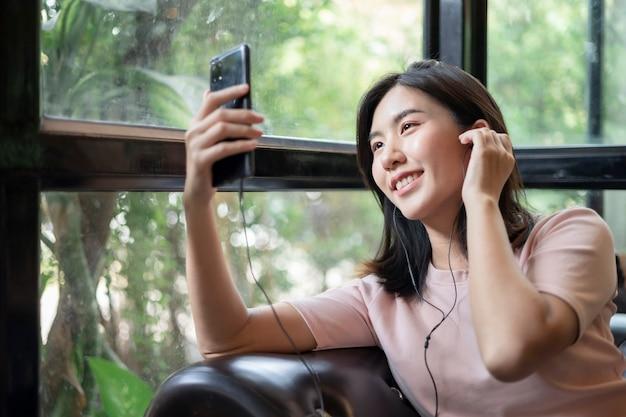 Jonge aziatische vrouwen werken via mobiele telefoons. aziatische vrouw die hoofdtelefoons draagt en aan muziek op haar mobiele telefoon luistert.