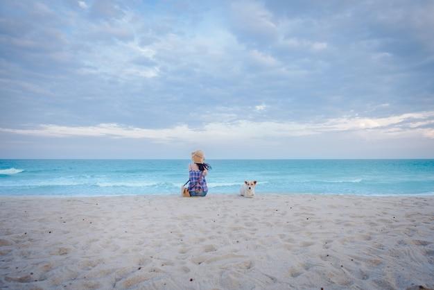 Jonge aziatische vrouwen zitten verdrietig aan het strand bij de zee met een hond, zittend op het strand op de achtergrond