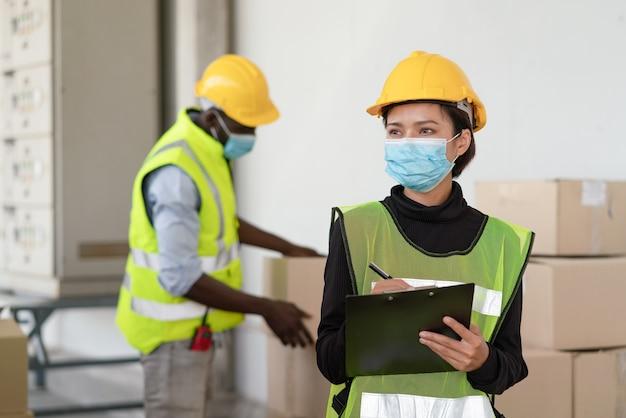 Jonge aziatische vrouwenarbeider draagt gezichtsmasker voor bescherming van het coronavirus bij logistiek magazijnfabriek