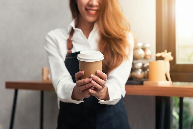 Jonge aziatische vrouwenbarista die een beschikbare koffiekop met het glimlachen gezicht houden bij koffieachtergrond