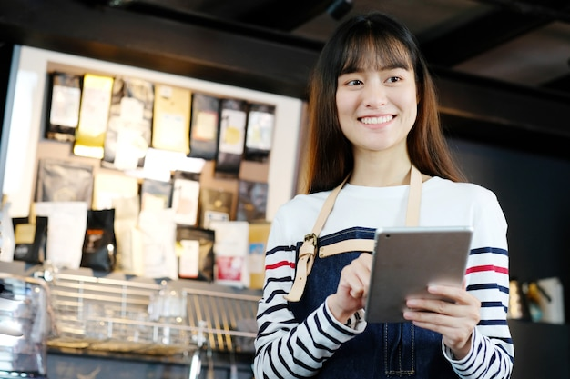 Jonge aziatische vrouwenbarista die tablet gebruiken.