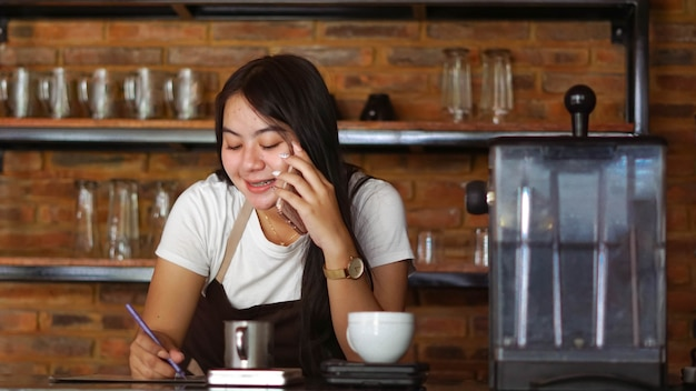 Jonge aziatische vrouwenbarista draagt schort die spreekt en ontvangt orde van klant op mobiel bij coffeeshop. concept van café winkel klein bedrijf. vrouwelijke barman notitie schrijven tijdens het luisteren naar de klant