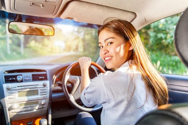 Jonge aziatische vrouwenbestuurder die een auto op de weg in platteland drijven