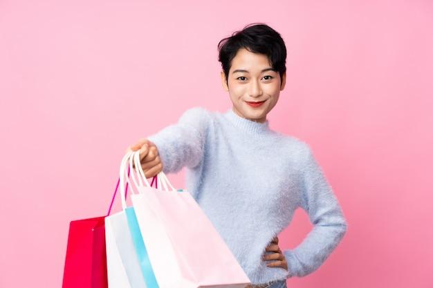 Jonge aziatische vrouwenholding het winkelen zakken en het geven van hen aan iemand