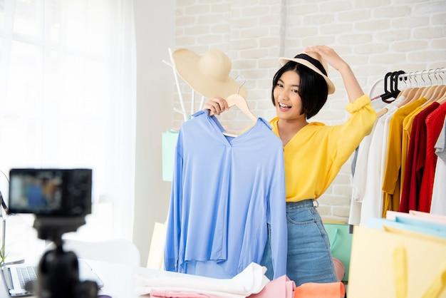 Jonge aziatische vrouwenmode vlogger die op kleren en toebehoren probeert