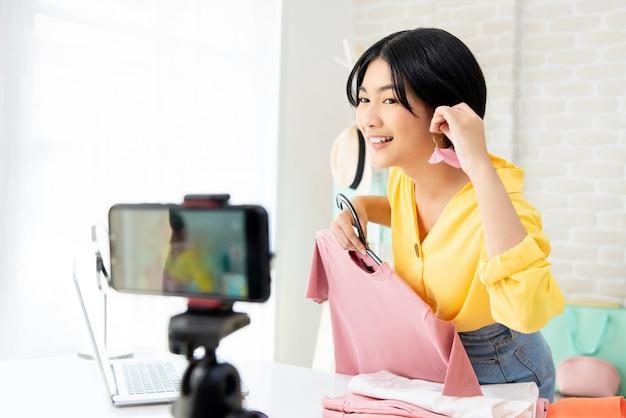 Jonge aziatische vrouwenmode vlogger die op oorring proberen