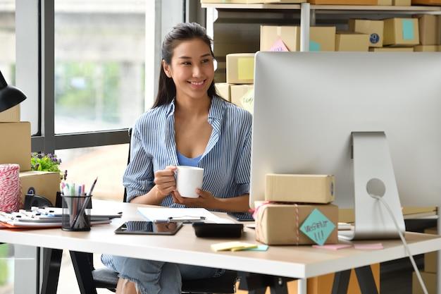 Jonge aziatische vrouwenondernemer bedrijfseigenaar die met computer thuis werken