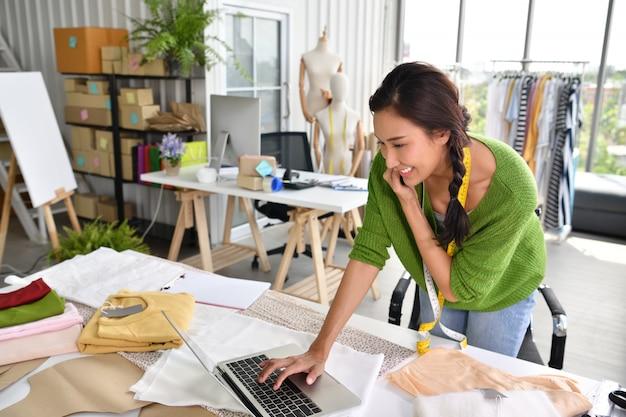 Jonge aziatische vrouwenondernemer / manierontwerper die in studio werkt
