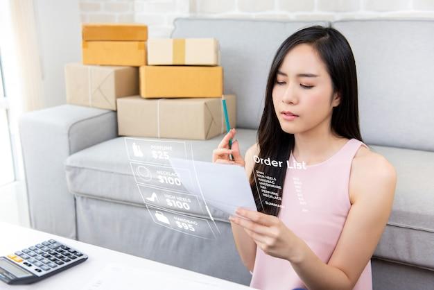 Jonge aziatische vrouwenondernemer of freelance online verkoper die orden thuis controleert