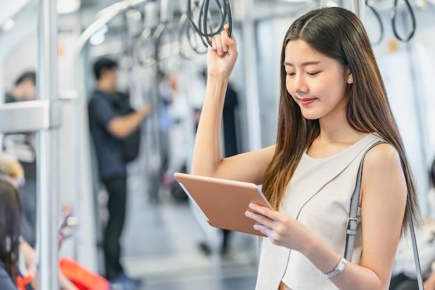 Jonge aziatische vrouwenpassagier die mutimedia speler via technologietablet gebruiken
