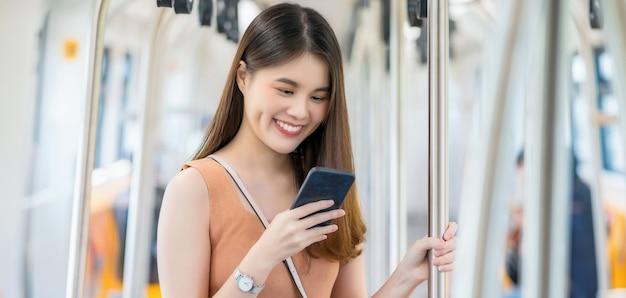 Jonge aziatische vrouwenpassagier die slimme mobiele telefoon met behulp van en aan buiten de metro kijken