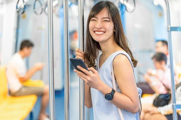 Jonge aziatische vrouwenpassagier die sociaal netwerk via slimme mobiele telefoon in metro gebruiken