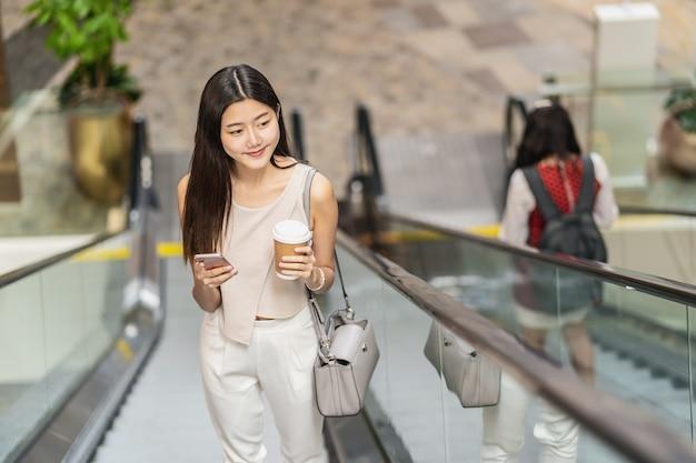 Jonge aziatische vrouwenpassagier gebruikend slimme mobiele telefoon en omhoog lopende roltrap