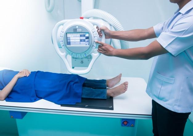 Jonge aziatische vrouwenpatiënt die in x-ray machine liggen. radiografie