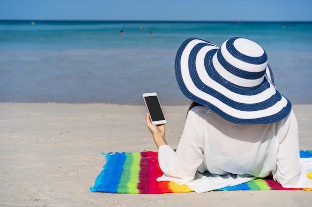 Jonge aziatische vrouwenreiziger die haar smartphone gebruiken bij tropisch zandstrand, het concept van de de zomervakantie
