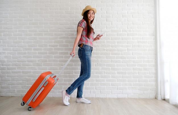 Jonge aziatische vrouwenreiziger die slimme telefoon en bagage in witte ruimte houden.