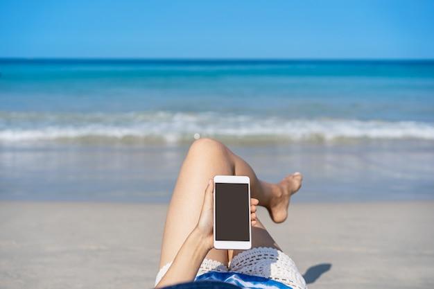 Jonge aziatische vrouwenreiziger gebruikend haar smartphone en zonnebaadt bij tropisch zandstrand, het concept van de de zomervakantie