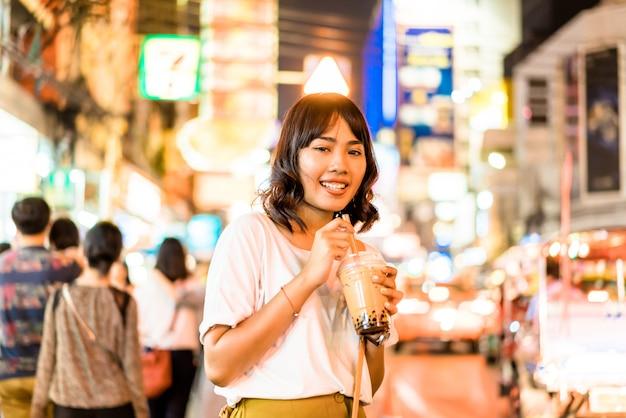 Jonge aziatische vrouwenreiziger met mening in china town in bangkok, thailand