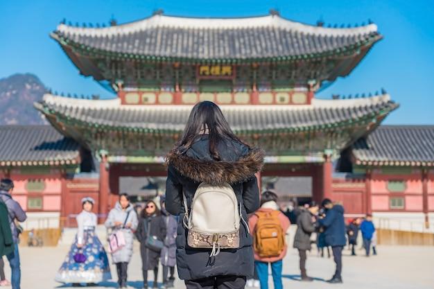 Jonge aziatische vrouwenreiziger met rugzak die in het gyeongbokgung-paleis reizen