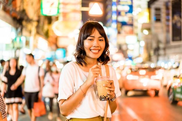 Jonge aziatische vrouwenreiziger met uitzicht op chinatown in bangkok, thailand
