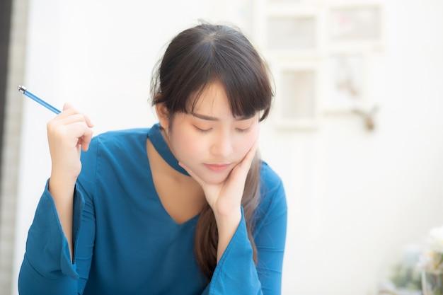 Jonge aziatische vrouwenschrijver die en op notitieboekje denken schrijven.