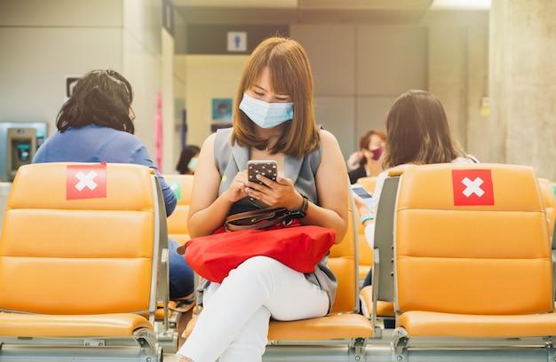 Jonge aziatische vrouwentoerist die gezichtsmasker draagt op luchthaven tijdens covid-19-virusuitbraak